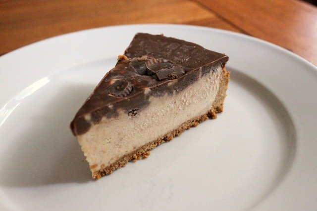 Slice of peanut butter ice cream cake with a graham cracker crust and covered in a layer of ganache and peanut butter cups.