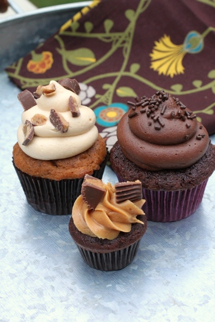 Three cupcakes on a galvanized platter. The one in front is a Peanut Butter Dulce de Leche Cupcake.