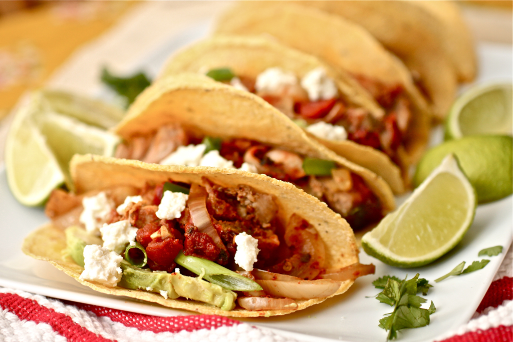 Smoky pork tinga tacos are lined up on a white plate with two wedges of lime next to them. The corn taco shells are filled with pork tinga, avocado, queso fresco, and fresh cilantro. There is a red and white striped napkin under the plate.
