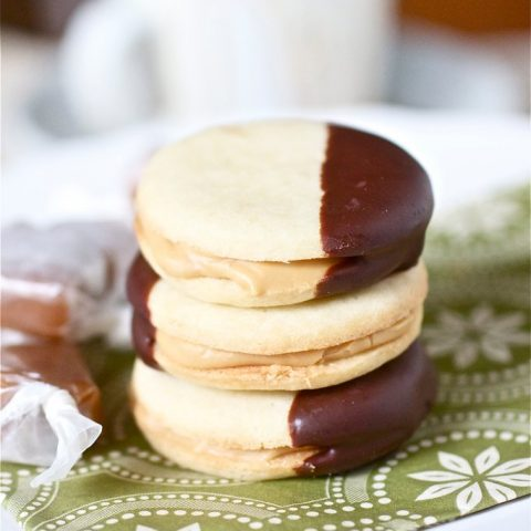 Photo of a stack of Butter Cookies with Dulce de Leche Filling. The cookies are dipped in dark chocolate.