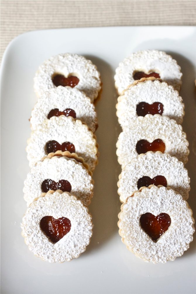 Plate of Linzer cookies with raspberry jam lined up in 2 rows.