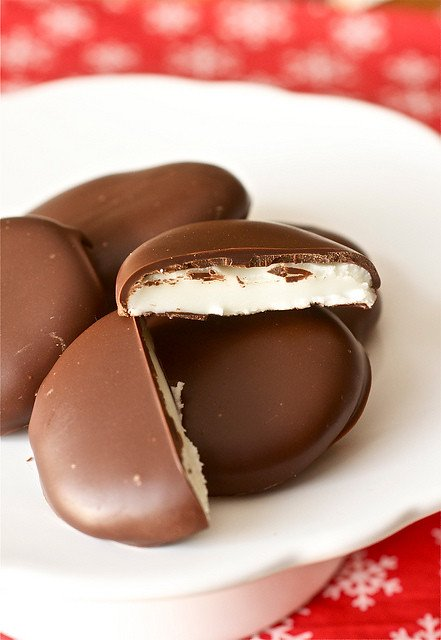This homemade peppermint patty recipe is just like the York candies you buy in the store but so much better! This photo is a stack of the patties with one sliced in half to show the minty filling.