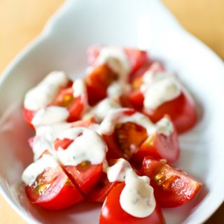 Chipotle ranch dressing is drizzled over quartered cherry tomatoes. The tomatoes are served in an oval white dish which is set on a wood table.