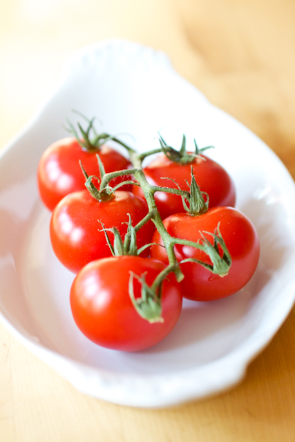 Garden cherry tomatoes on the vine. The tomatoes are set in an oval white serving dish which is set on a wood table.