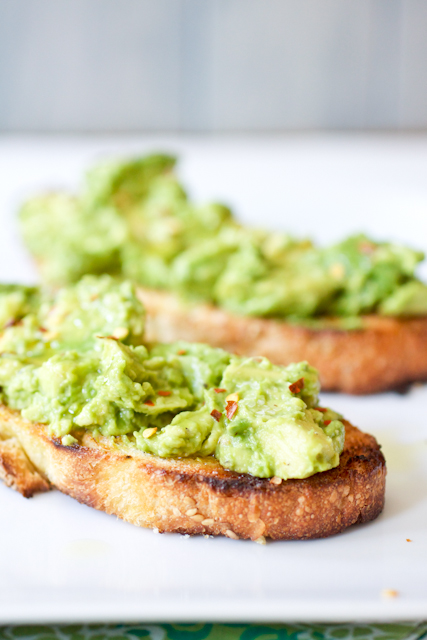 Two Spicy Smashed Avocado Toasts on a white plate.