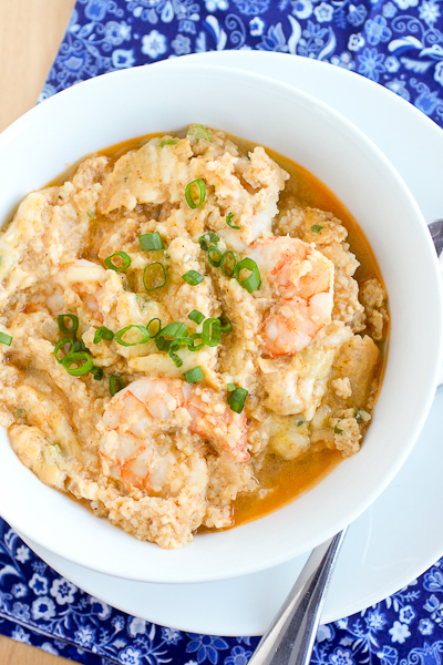 Overhead photo of One Pan Shrimp and Grits in a white bowl. The shrimp are baked into the grits and there's a sprinkle of fresh scallions on top of the grits.
