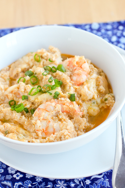 One Pan Shrimp and Grits in a white bowl. The shrimp are baked into the grits and there's a sprinkle of fresh scallions on top of the grits.