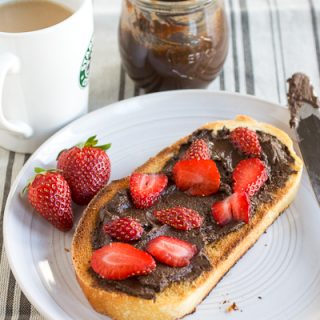 Peanutella Chocolate Peanut Butter Spread is slathered on a piece of toasted French bread and sliced strawberries are scattered on top. There are two strawberries and a knife on the round gray plate. There is a white cup of coffee and the jar of Peanutella in back of the plate on a gray striped napkin.