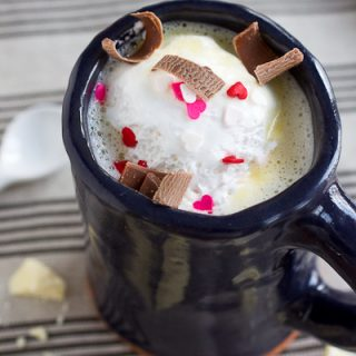White Hot Chocolate served in a dark blue handmade ceramic mug on a gray striped napkin. There is a dollop of Marshmallow fluff floating on top of the hot chocolate along with milk chocolate shavings and pink and white heart shaped sprinkles. On the napkin next to the cup, there is a small white spoon and hunks of white chocolate.