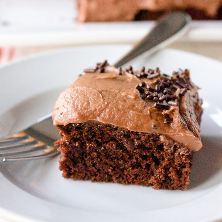 A square slice of No Bowl Mocha Snack Cake on a round white plate. The cake is covered with mocha frosting and has sprinkles around the edge.
