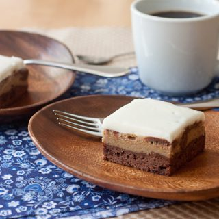Two Espresso Cheesecake Brownies set on oval acacia wood plates with a fork on each plate. There is a cup of coffee in the background in a white mug. The coffee and plates are set on a blue floral napkin. The brownies have a layer of fudgy brownie on the bottom, a layer of espresso cheesecake in the middle, and a layer of sour cream topping on top.