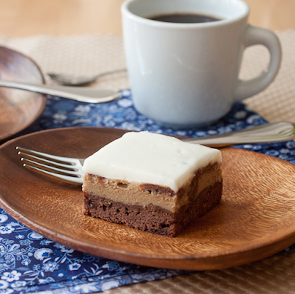 An Espresso Cheesecake Brownie set on an oval acacia wood plate with a fork on the plate. There is a cup of coffee in the background in a white mug. The coffee and plate are set on a blue floral napkin. The brownie has a layer of fudgy brownie on the bottom, a layer of espresso cheesecake in the middle, and a layer of sour cream topping on top.