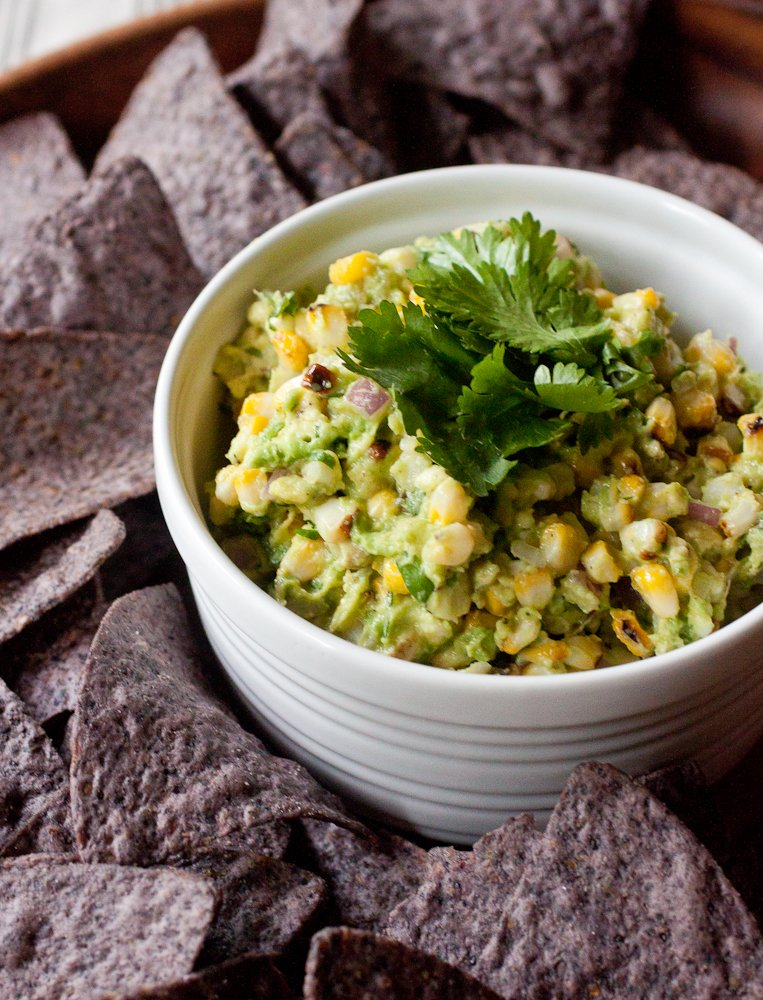 Bowl of grilled corn guacamole with fresh cilantro leaves on top and surrounded by blue corn tortilla chips.