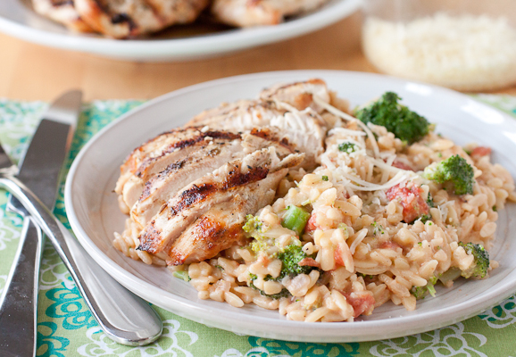 Herb Grilled Chicken with Creamy Broccoli Orzo on a round gray plate. The plate is set on a green floral napkin. There is a knife and fork next to the plate, and a bowl of grated Parmesan cheese and a plate of grilled chicken in the background of the photo.