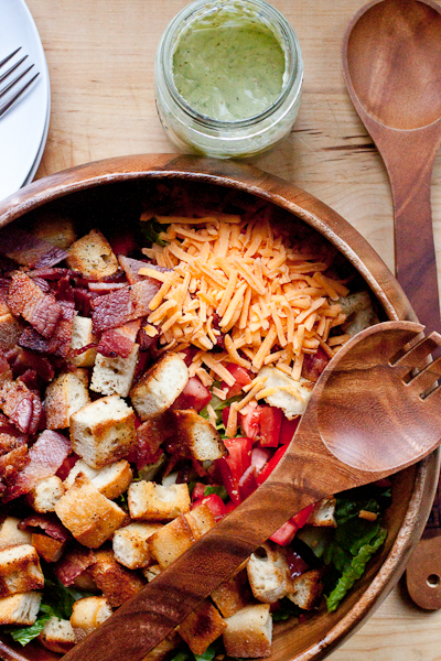 BLT Panzanella Salad in a round acacia wood bowl with salad tongs on top. There is a jar of ranch dressing and round white plates with forks next to the bowl.
