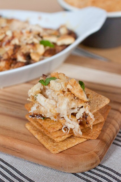 A stack of 3 Wheat Thins crackers with a scoop of Hot Crab Dip on the top cracker. There is a dish of the crab dip in the background and the crackers are sitting on top of a wood cutting board.
