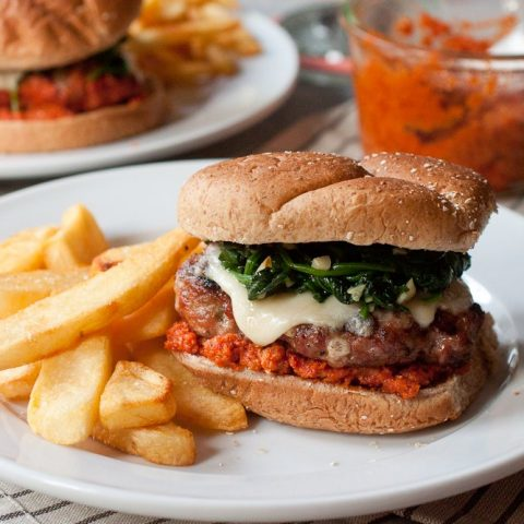 Pork sausage burgers piled high with garlicky spinach, romesco sauce, and melted cheese on a soft bun. There are thick-cut French fries on the plate with the burger.
