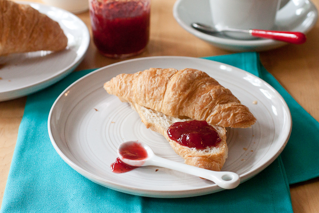 A schmear of Strawberry Vanilla Bean Jam on a croissant that has been sliced in half through the center. The croissant is on a round plate on top of a turquoise napkin. There is a small white spoon on the plate next to the croissant. In the background, there is another croissant, the jar of jam, and a cup of coffee in a white mug on a white saucer.
