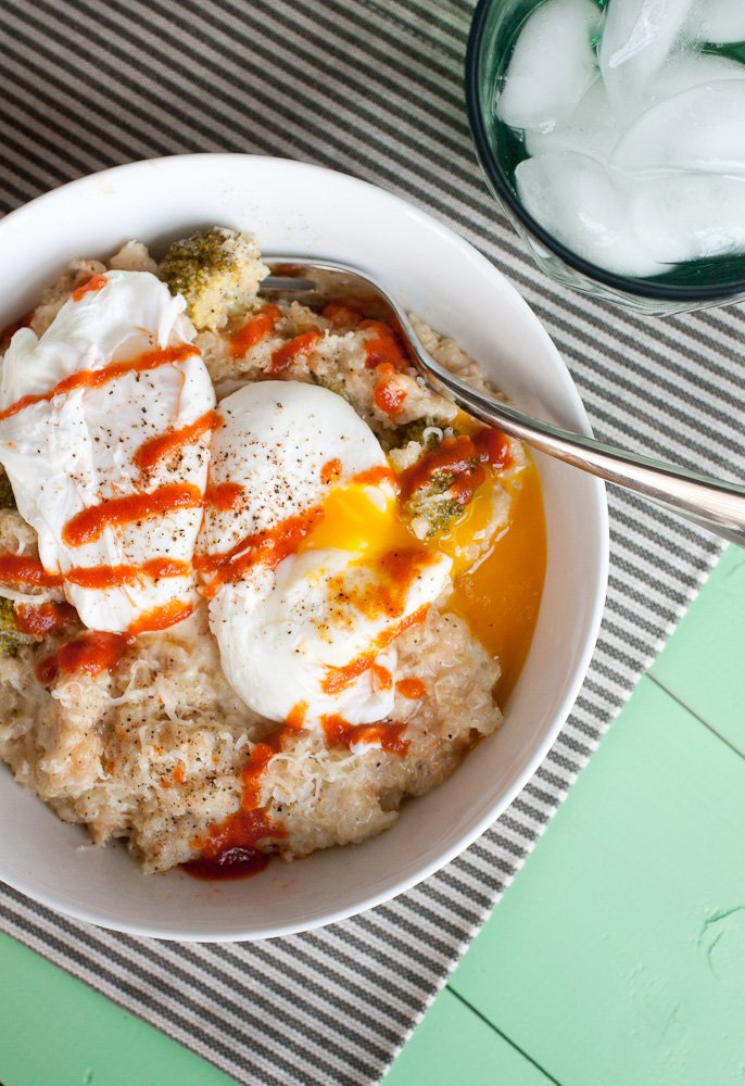 Cheesy Broccoli Quinoa with Sriracha and Poached Eggs in a bowl with a spoon. The bowl is on a striped napkin. The poached eggs are broken and the yolks are running into the quinoa.