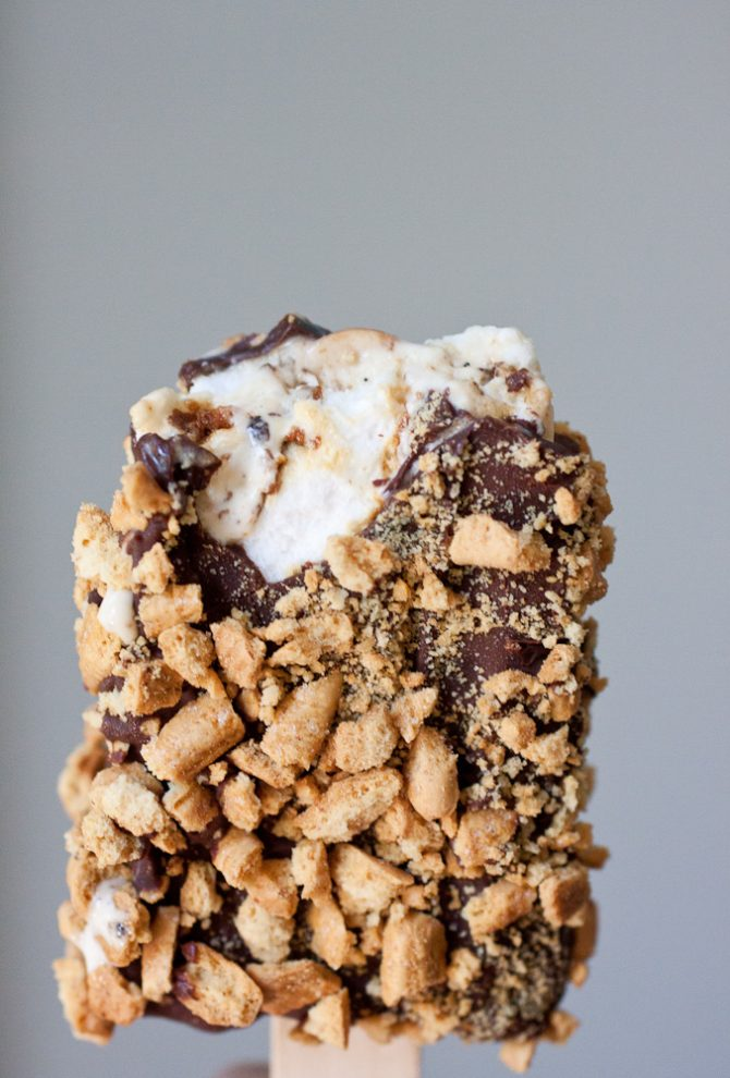 Toasted marshmallow ice cream popsicles coated in chocolate and rolled in crushed graham crackers.