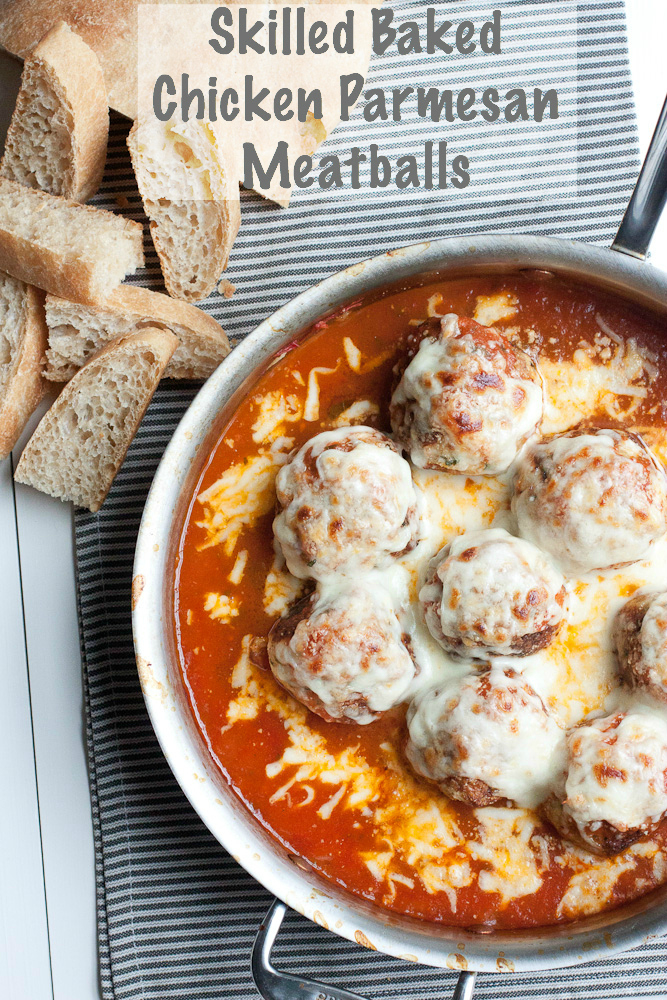Overhead Pinnable photo of Baked Chicken Parmesan Meatballs in a stainless steel saute pan, in a bed of marinara sauce and covered with melted mozzarella and parmesan cheeses. Next to the pan are a few slices of cut up ciabatta bread for dipping in the sauce. The pan and bread are sitting on a gray striped napkin on a white wood table.