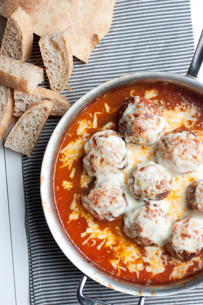Overhead photo of Baked Chicken Parmesan Meatballs in a stainless steel saute pan, in a bed of marinara sauce and covered with melted mozzarella and parmesan cheeses. Next to the pan are a few slices of cut up ciabatta bread for dipping in the sauce. The pan and bread are sitting on a gray striped napkin on a white wood table.