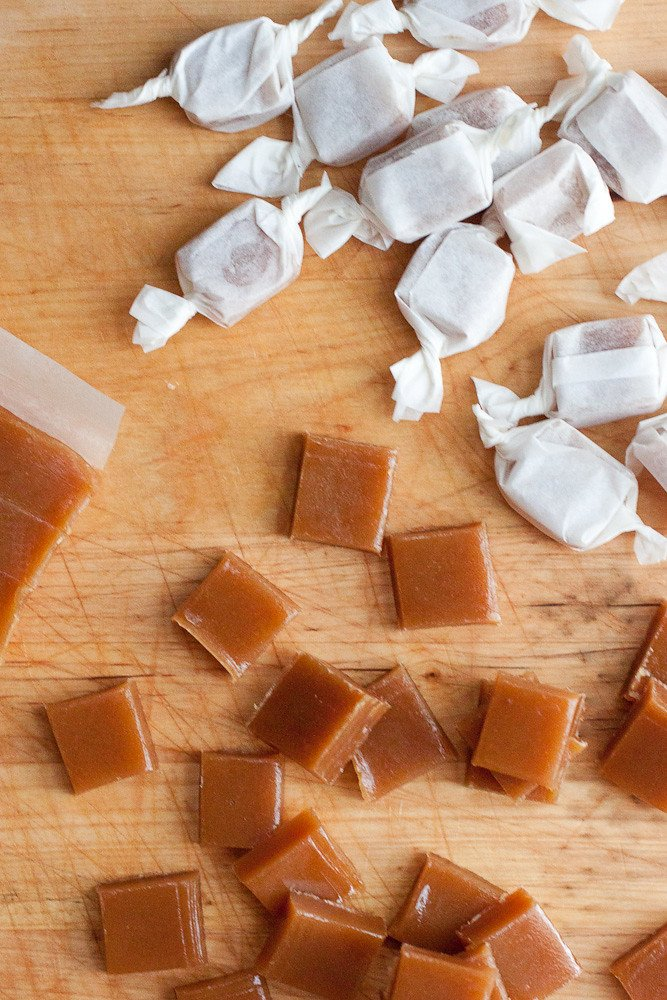Apple Cider Caramels on a cutting board that are wrapped and unwrapped.