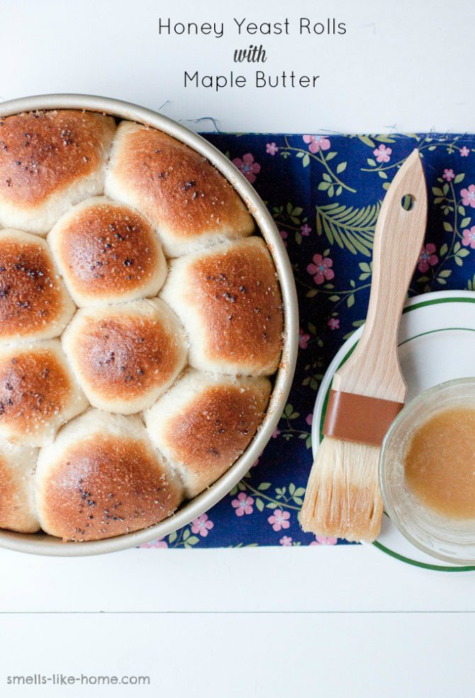 Pinnable image of Pan of honey yeast dinner rolls brushed with maple butter and sprinkled with sea salt.
