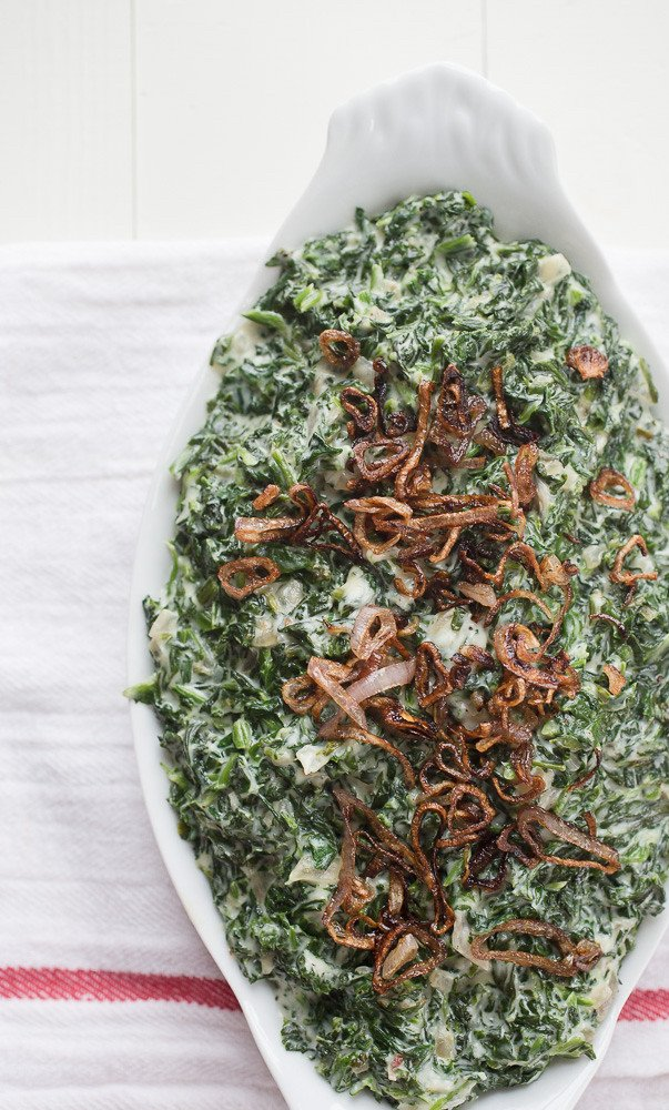 Steakhouse Creamed Spinach Recipe in a bowl with crispy shallots on top. This is the best creamed spinach recipe for Thanksgiving!