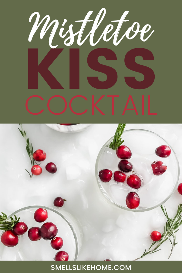 Pinnable image of The Mistletoe Kiss cocktail. This holiday drink is made with vodka, rosemary simple syrup, and a garnish of fresh cranberries.