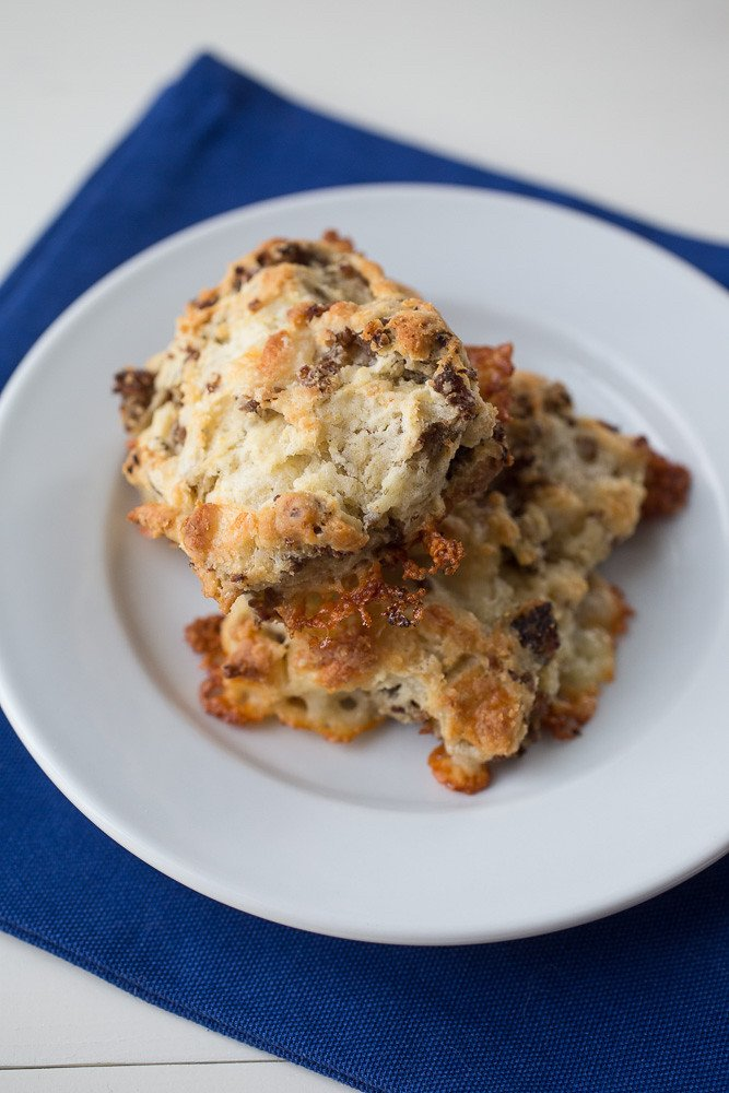 Sausage and Cheddar Biscuits stacked on a plate.