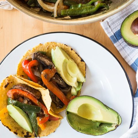 Portobello and Poblano Fajitas on a plate served in a corn tortilla with avocado for an easy vegan fajita meal.