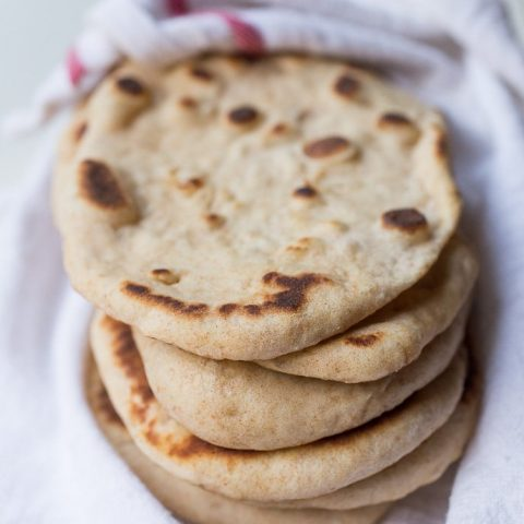 A stack of homemade naan bread wrapped in a kitchen towel to keep it warm.