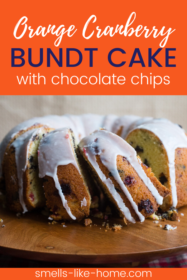 Pinnable image of an orange cranberry bundt cake with chocolate chips. The cake has a vanilla glaze on top and slices cut out of it.