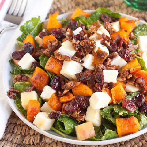 Fall harvest salad in a bowl. The salad contains a base of baby kale with roasted butternut squash, cubed brie, Honeycrisp apples, candied pecans, dried cranberries, and maple dijon vinaigrette on top.