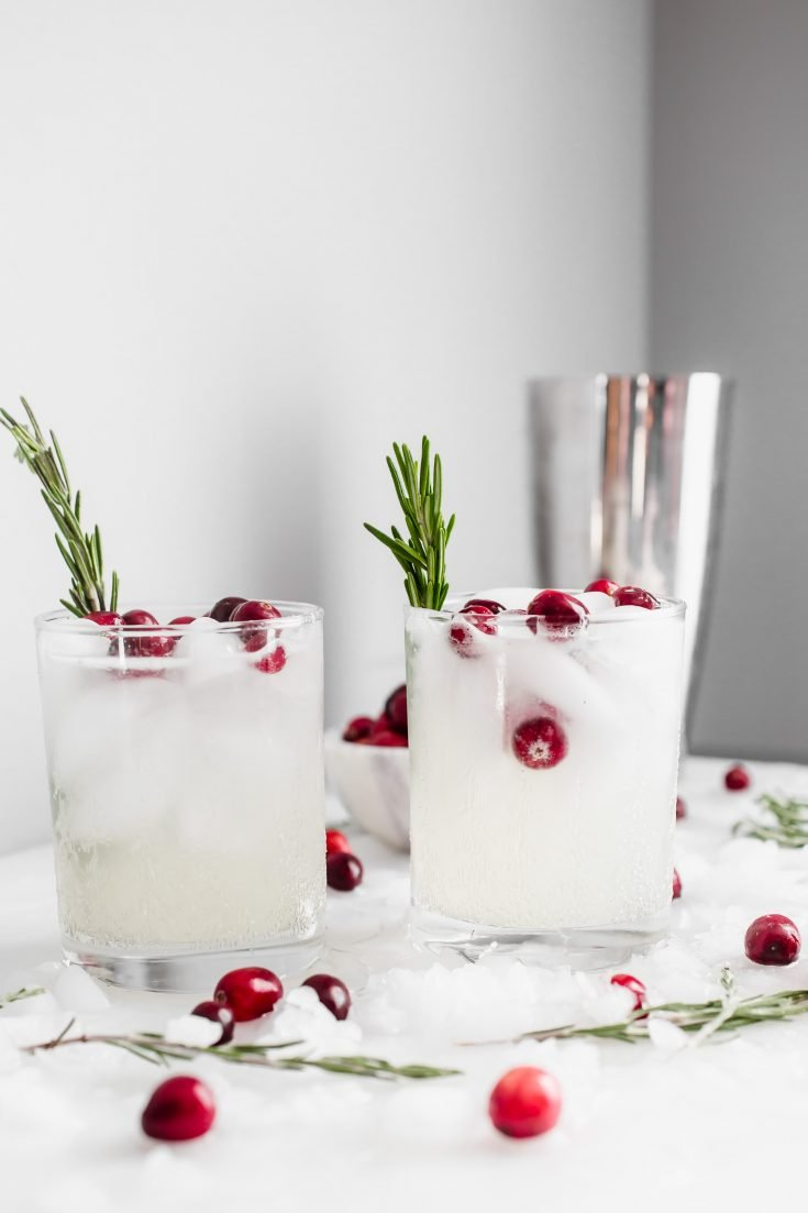 The Mistletoe Kiss Holiday Drink - a simple mix of vodka, lemon juice, and a holiday-inspired secret weapon ingredient. #holiday #drink #cocktail #christmas #mistletoe #kiss #booze #party #vodka #cranberry #simplesyrup #rosemary #largebatch