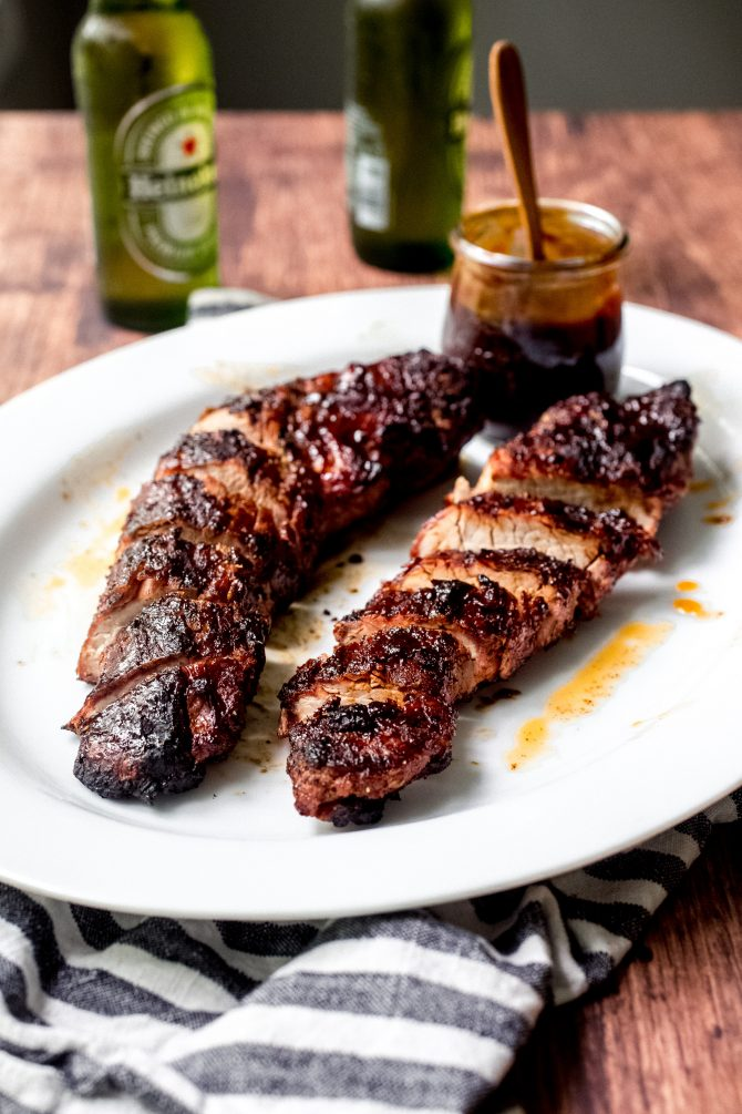 Bourbon peach BBQ grilled pork tenderloin is the perfect way to cook a pork tenderloin. The BBQ sauce, with it's sweet peaches and smoky bourbon flavor, adds a rich glaze to the pork, leaving it utterly irresistible. #grilled #pork #tenderloin #BBQ #bourbonpeach #BBQsauce #summer #entertaining #recipe
