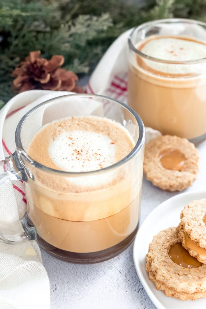 Two homemade eggnog lattes in glass mugs with holiday sandwich cookies and garland