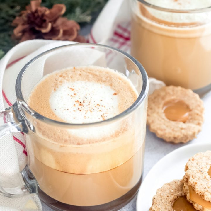 Eggnog lattes in clear glass mugs with cookies on a plate on the side. This eggnog latte recipe is made with real eggnog that you'll heat and froth before adding to 2 shots of hot espresso.