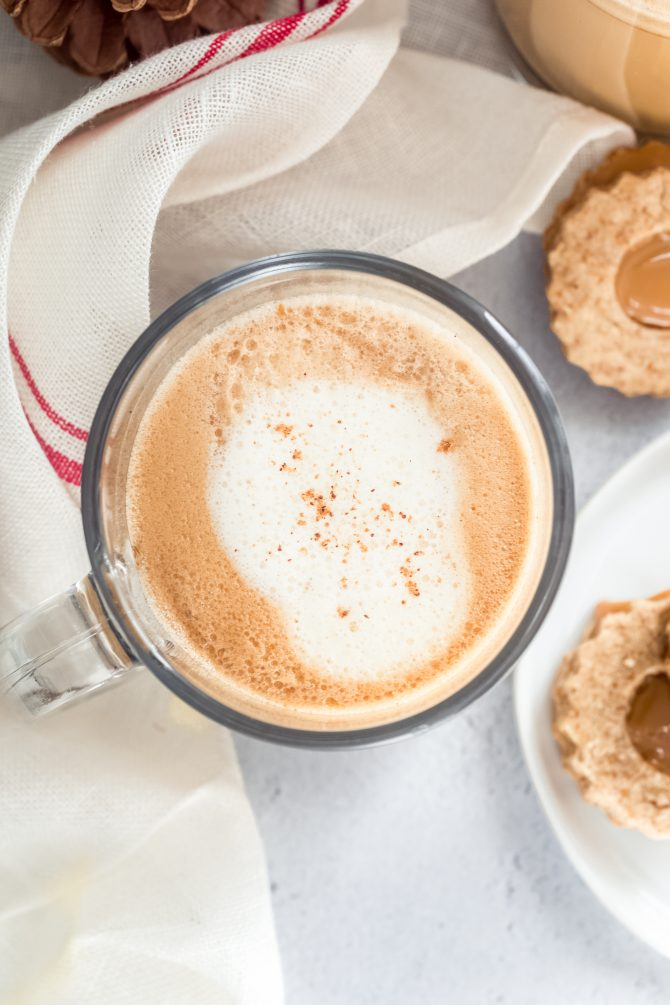 Overhead shot of a foamy eggnog latte sprinkled with nutmeg and cinnamon