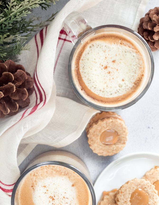 Two eggnog lattes with foam next to pinecone decorations and Christmas cookies