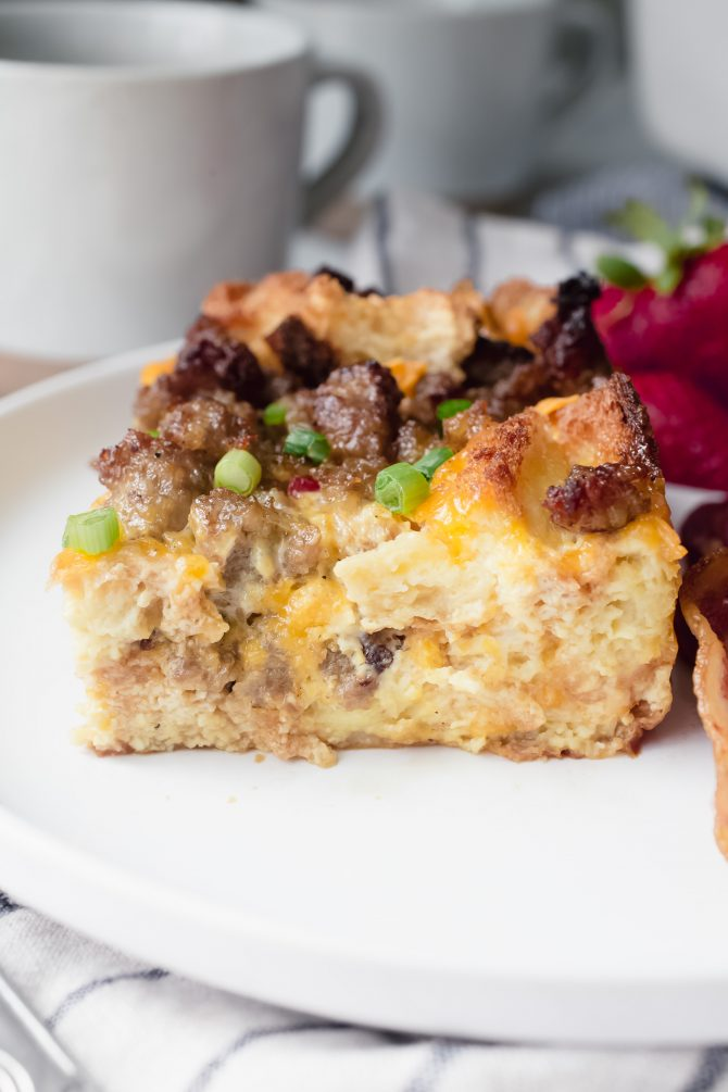 Close-up shot of a slice of sausage, egg, and cheese breakfast casserole garnished with green onions
