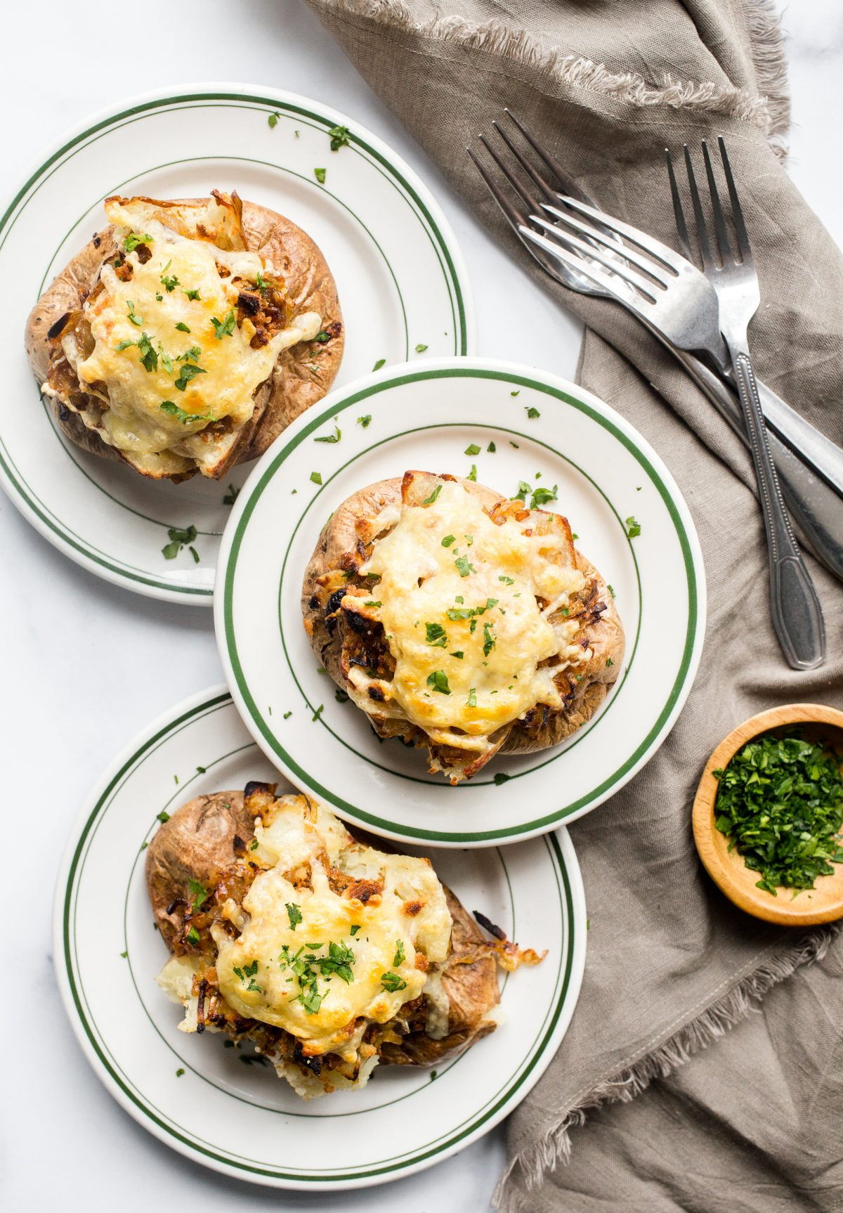 3 loaded French onion soup baked potatoes on small plates with forks and a bowl of parsley