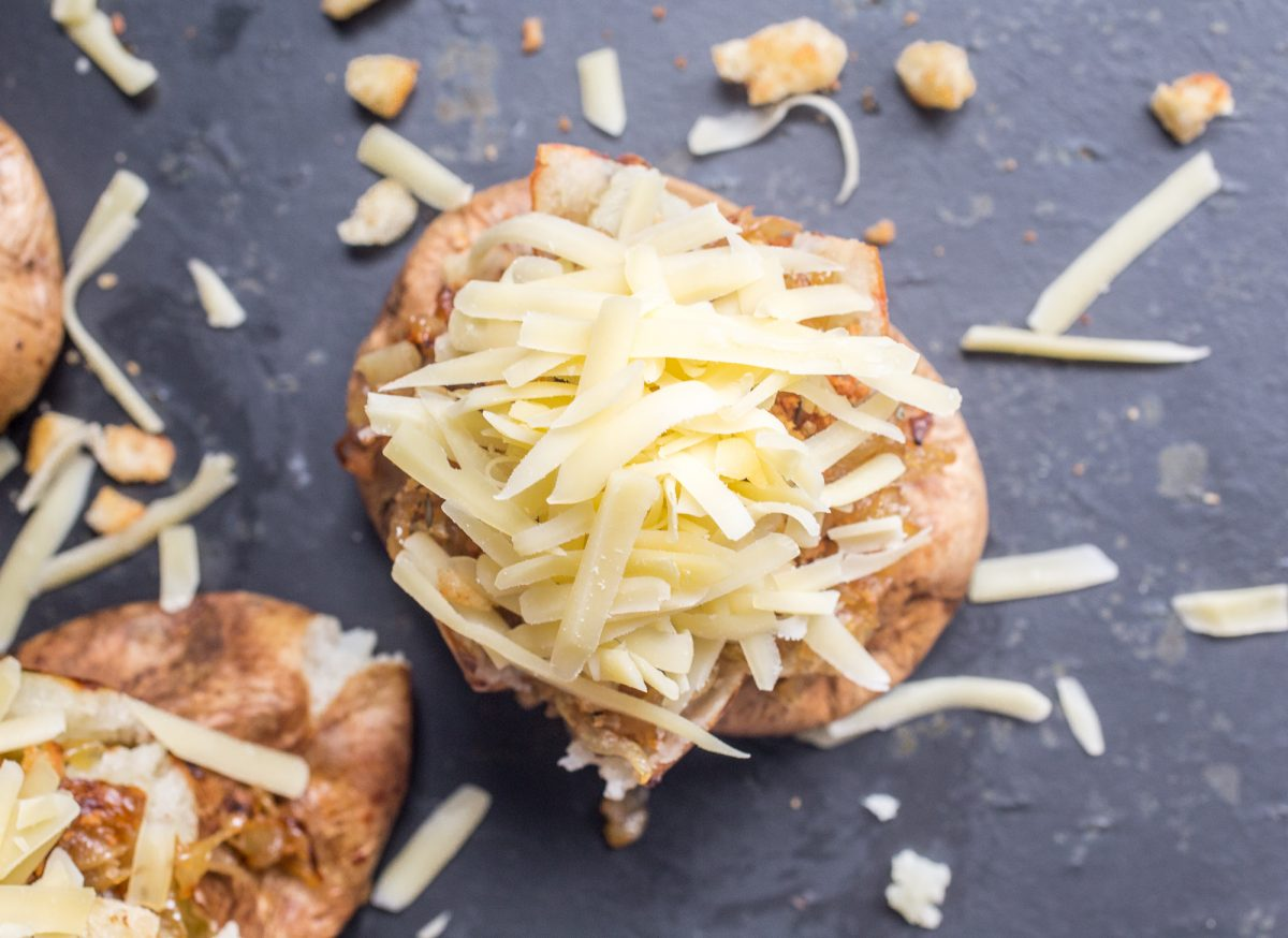 Baked potatoes loaded with onions and shredded gruyere cheese