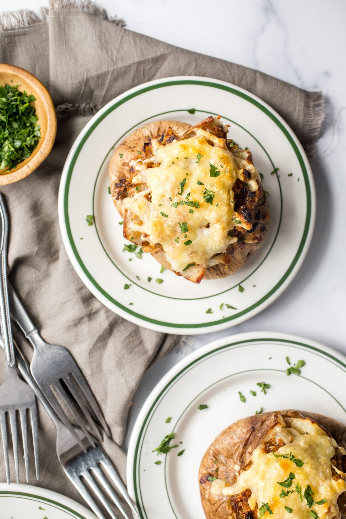 2 loaded baked potatoes stuffed with caramelized onions and gruyere cheese on small white plates