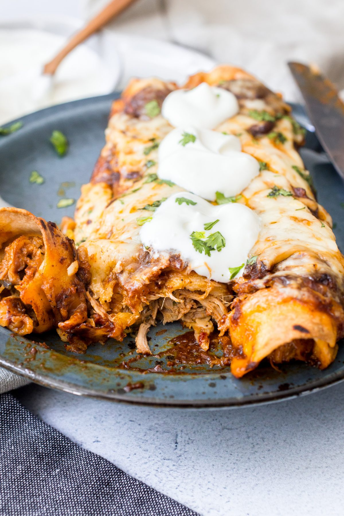 Close-up shot of 2 enchiladas filled with shredded chicken and garnished with sour cream