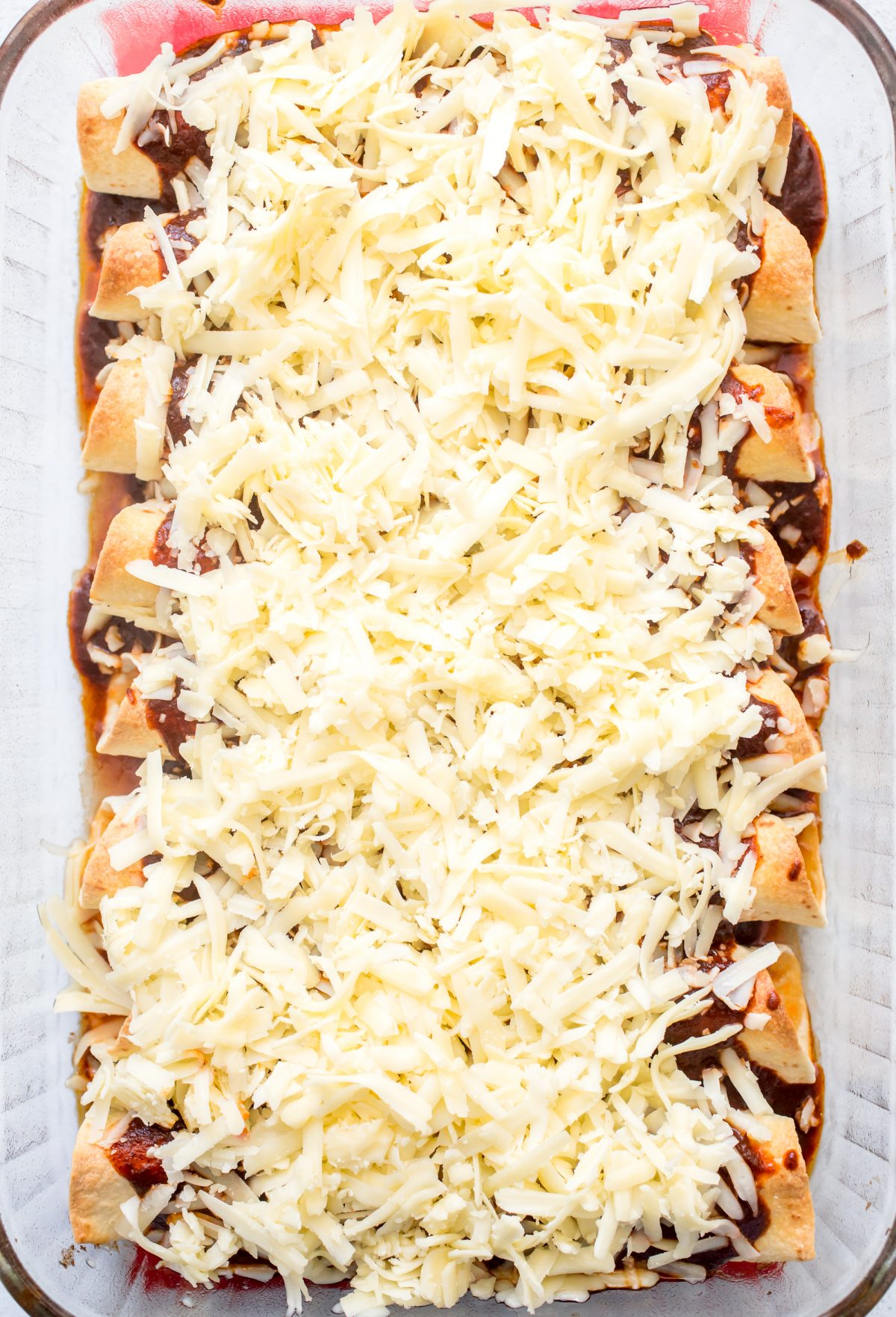 Enchiladas covered in red sauce and shredded cheese ready to be baked