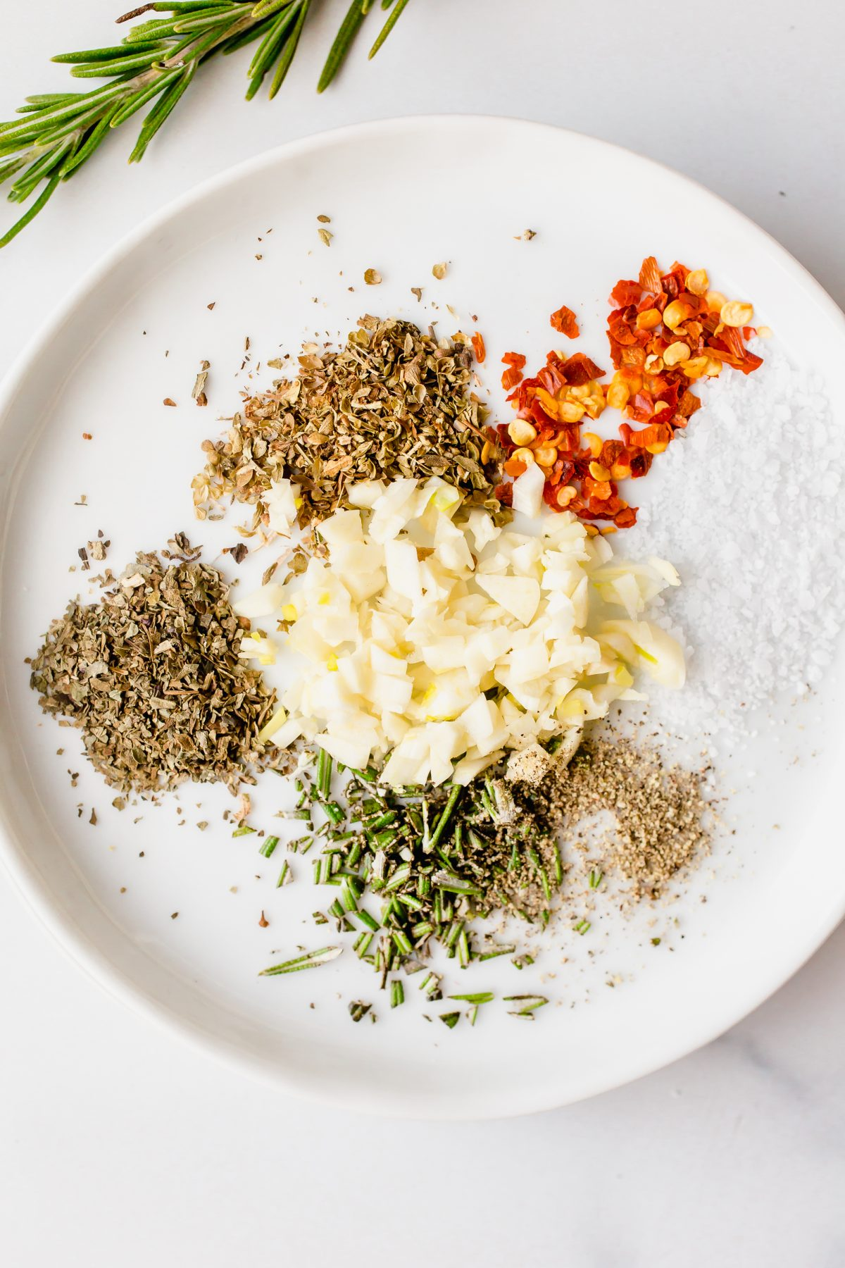 A round white plate with garlic, rosemary, salt, pepper, crushed red pepper, oregano, and basil