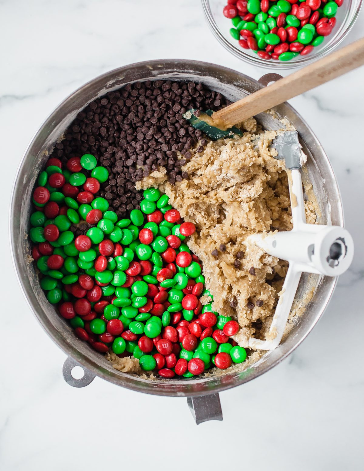 A stand mixer bowl with cookie dough, chocolate chips, and Christmas M&Ms