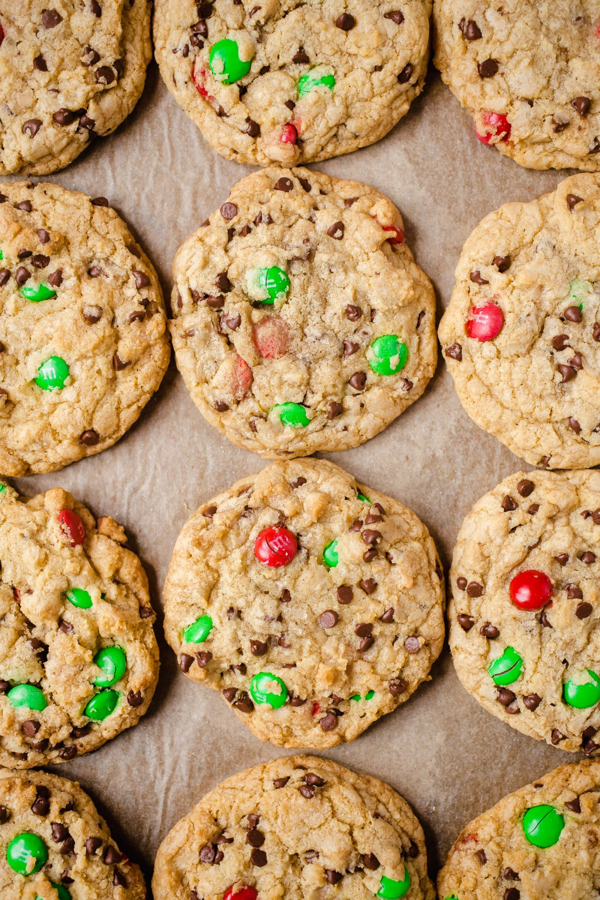 12 large chocolate chip and M&M Christmas cookies on parchment paper